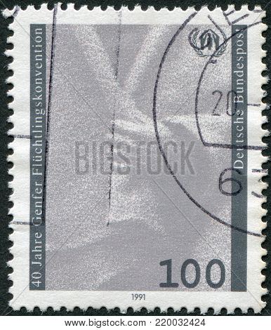 GERMANY - CIRCA 1991: A stamp printed in Germany, dedicated to 40th anniversary of the Geneva Convention on Refugees, shows a hand holding cloak and emblem, circa 1991