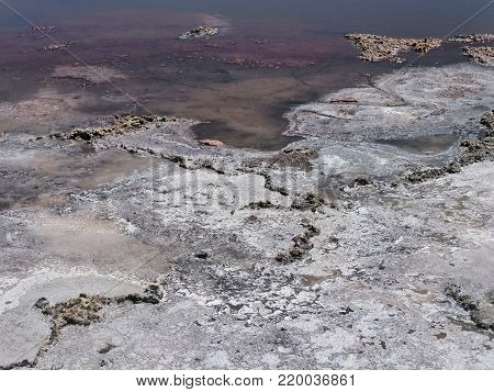 Abstract background texture of solitary earth and pink water thermal spring.