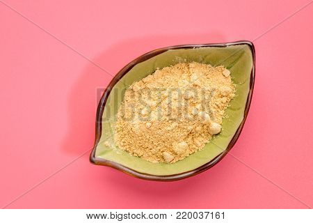 maca root powder in a leaf shaped bowl against pink background