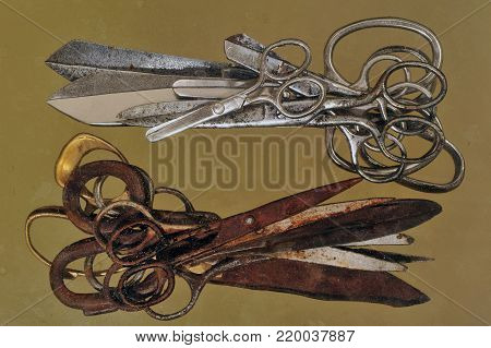 Two heaps of metal scissors are different sizes: from below are old rusty scissors, from above are new shiny silver scissors.