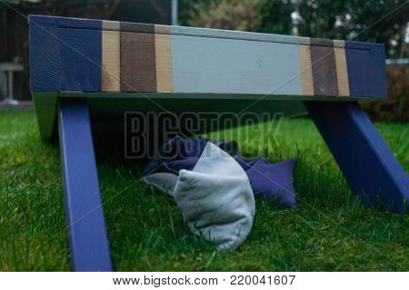 Backside Of Purple Wooden Cornhole Game Board With Beanbags On Grass