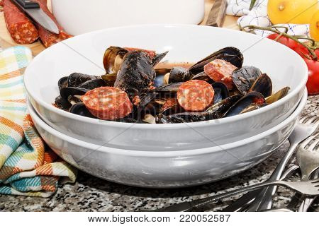 warm spanish mussel soup with sliced chorizo and tomato sauce