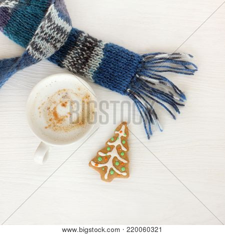 white mug with frothy cappuccino, blue scarf and ginger fir tree top view / warming winter coffee break