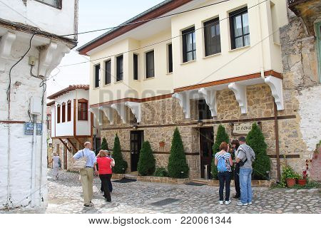KASTORIA, GREECE - SEPTEMBER 17, 2012: These are undifined tourists on one of the streets in the old part of a small provincial town not in the north of the province of Macedonia.