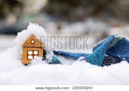 small wooden house and blue scarf on the background of snow-covered landscape / warm clothes for warming in winter