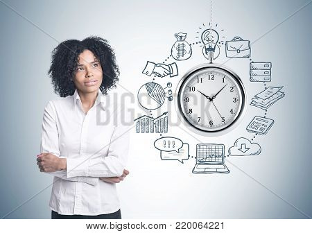 Portrait of a thoughtful African American businesswoman wearing a white blouse and standing with crossed arms. A gray wall with a time management sketch