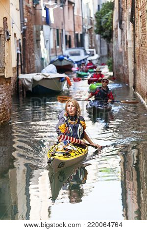 VENICE, ITALY - SEPTEMBER 22, 2017: City tour by tourists with kayak, narrow channel. Communication in the city is done by water, which creates a network of 150 channels interconnected.