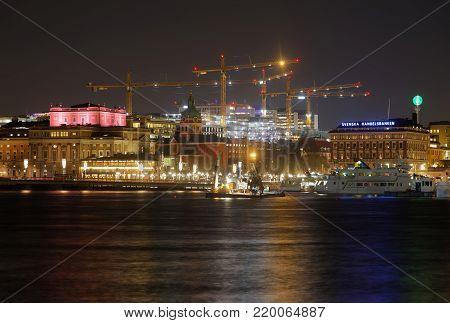STOCKHOLM, SWEDEN - DEC 27, 2017: Nightscape of central Stockholm. Old buildings, sea and construction cranes. Sweden, December 27, 2017
