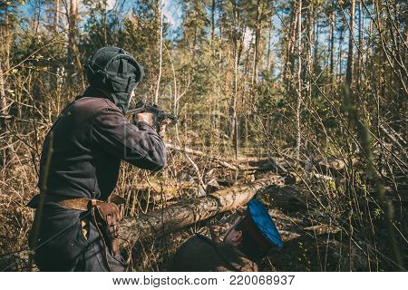 Unidentified Re-enactors Dressed As Soviet Russian Red Army Infantry Soldiers Of World War II Hidden Firing At Enemy In Spring Forest At Historical Reenactment
