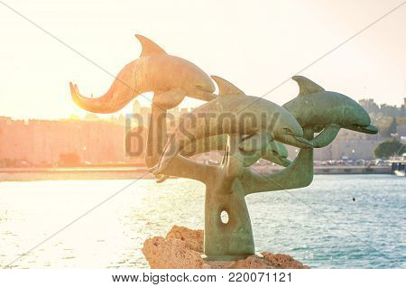 RHODES, GREECE - August 26: Dolphin statue at the beach in Kolona harbor outside the Old Town with burning sun on August 26, 2017 in Rhodes city, Greece