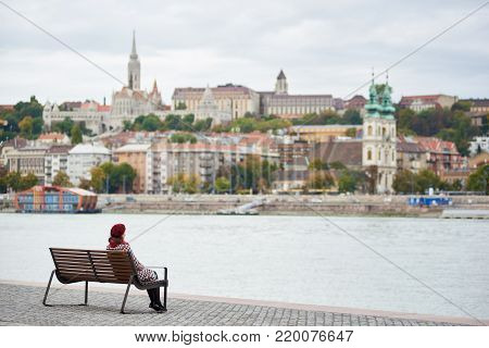Girl In Red Beret Sits On A Bench On The Embankment Of Budapest Near River And View Of Buda Side Of