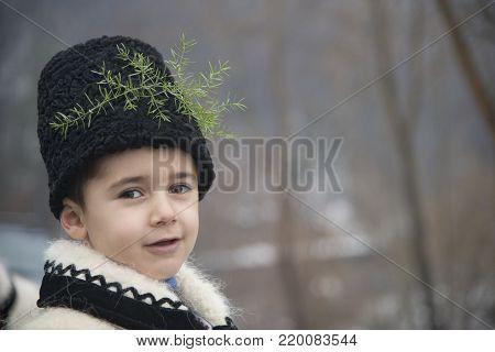 Barsana, Maramuresh/Romania - 12.25.2017: The boy dressed in winter traditional Romanian (Maramuresh region) clothes. Portrait. Image has free space for text.