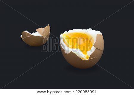 A photo of boiled smash broken hen beige egg isolated on dark blue. Egg's liquid yolk photo, bright contrast