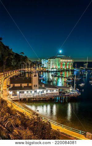 Avalon Bay Casino lit up as dusk settles over yacht club pier.