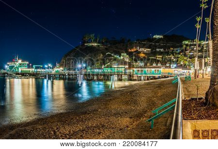 Avalon Pier on Catalina Island in California with night lights reflecting through the ocean pilings along the boardwalk.