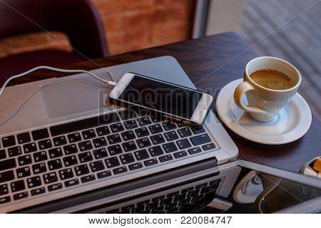 A laptop's keyboard, smartphone and a cup of coffee.