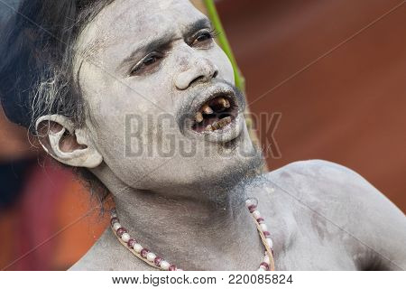 BABUGHAT, KOLKATA, WEST BENGAL / INDIA - 10TH JANUARY 2015 : Portrait of Hindu Sadhu with holy ash applied on face and body, aginst brown background.