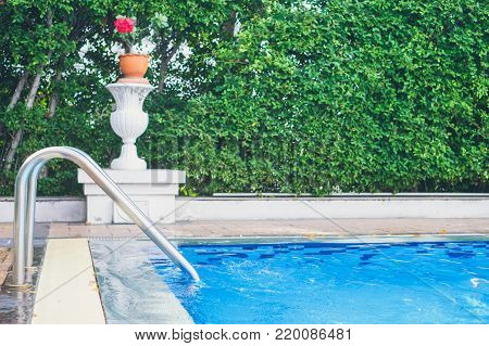 Swimming pool with stair at home, safety rails by a swimming pool decorated by bush and red flower / filmed tone
