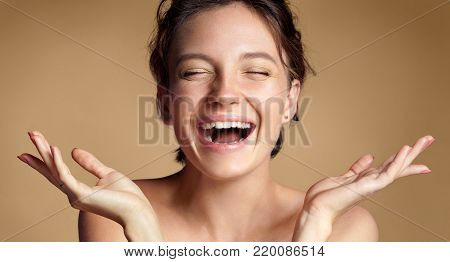 Happy woman with perfect skin. Photo of brunette girl showing empty copy space on beige background. Youth and Beauty