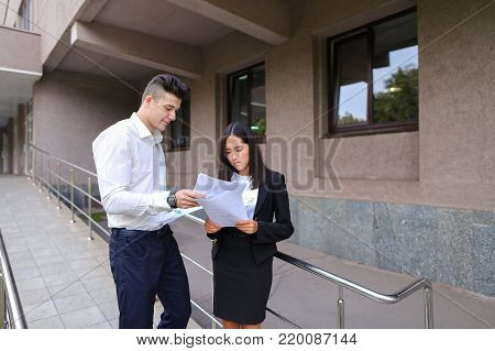 Two young educated boy and girl, successful entrepreneurs, students communicate, negotiate working moments, see into plans, kept in hands paper, graphics and view them, stand on background of office buildings outdoors. Girl with dark hair dressed in white