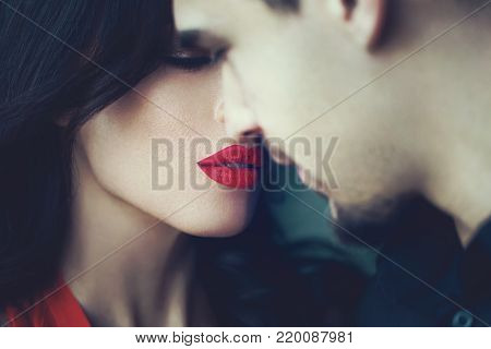 Woman with red lips closing eyes before kissing young man closeup