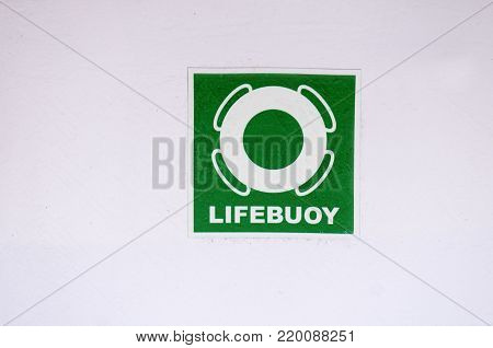 White symbol of a life buoy on a green background. Approval mark for cruise ship passengers.