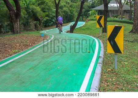 Beautiful green bicycle lane with roadsign in the park. (Selective focus)