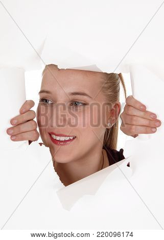A smiling face of a young woman peeking through a hole in a paper