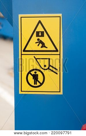 Warning sign on farm machinery.To keep the distance. It is forbidden to stand under the bucket. It is possible to fall. It is possible to obtain a blow on the head.