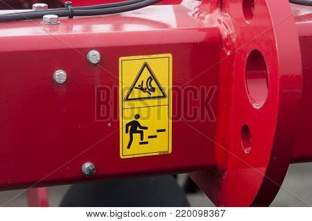 Warning sign on agricultural machinery. It is forbidden to climb when the engine is switched on, it is possible to get injured.