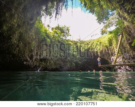 Upolu Island, Western Samoa, South Pacific - October 27, 2017: Tourists in the To Sua Trench - the volcanic swimming hole is a popular travel destination, accessed via a steep ladder.