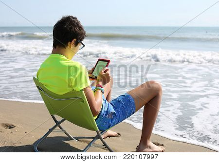 Young Boy Reads An Ebook By The Ocean In Summer