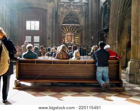 VIENNA, AUSTRIA - OCTOBER 16, 2005: People pray in the St. Stephen's Cathedral in Vienna on October 16, 2005.