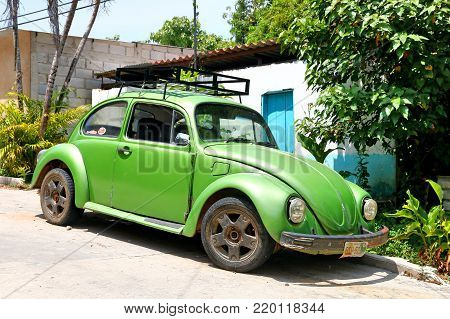 Palenque, Mexico - May 23, 2017: Green retro car Volkswagen Beetle in the town street.