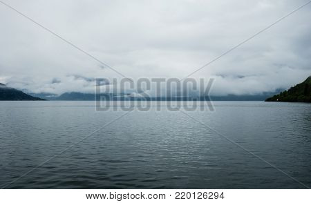 Low clouds over water between sloping hills in Hardangerfjord, Norway.