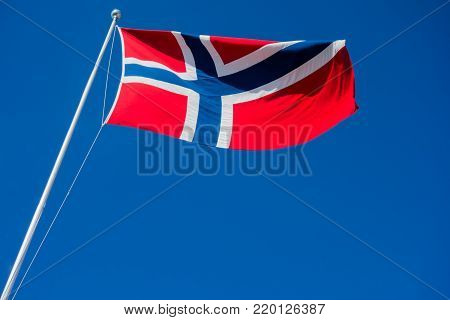 Flag of Norway on pole flapping in wind against clear blue sky.