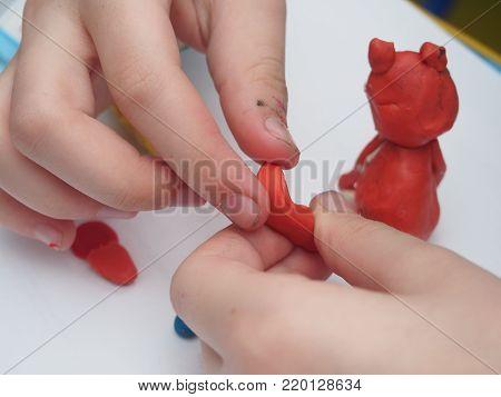 Child sculpts a figure out of plasticine. Children's artistic creativity. Close-up. Hobbies.