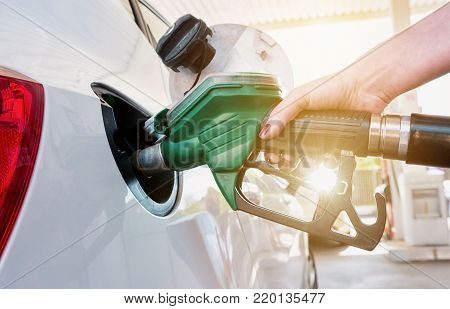 Woman refueling her car at a gas Station with explosiv sunlight in the background. ideal for websites and magazines layouts