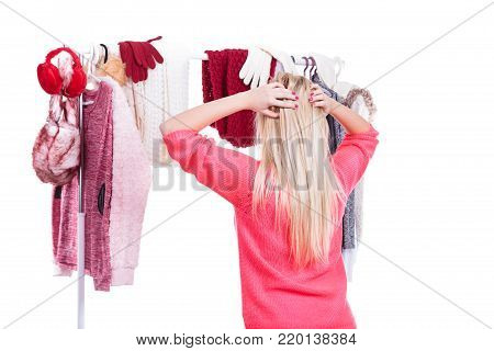 Young woman standing in wardrobe or in mall shop, choosing warm clothes, deciding what to wear or buying. Picking winter autumn clothing concept. Back view