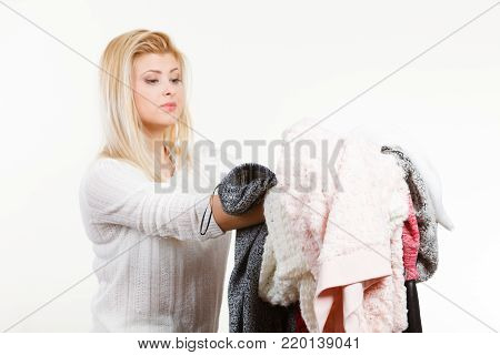 Fashion, clothes dilemmas concept. Woman holding big pile of warm winter clothing, cant decide what to wear, on white grey