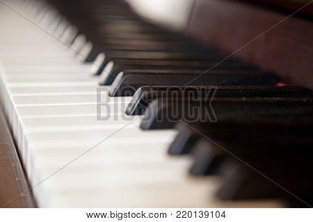 Close up of dusty old black and white piano keys on a brown wooden piano with selective focus and space for text.