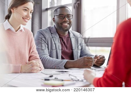 Serious Dark Skinned Male Model In Formal Clothes Looks Attentively At Female Assistant, Indicates O