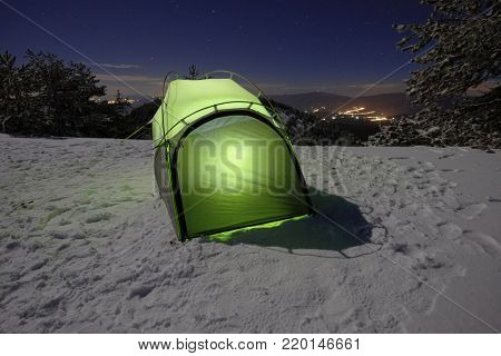 illuminated green tent on the snow at night in Etna Park, Sicily