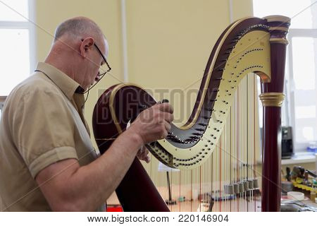 ST. PETERSBURG, RUSSIA - AUGUST 8, 2017: Master tuning the harp in Resonance Harps enterprise. The company revives the production of harps of the Lunacharsky factory founded in 1947