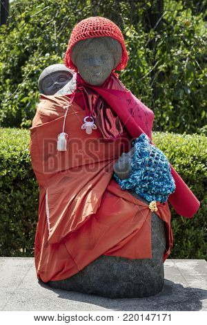 Tokyo - Japan, June 3, 2017: Traditional stone carved Jizo with red skirt and hat carrying children at the Sensoji temple grounds