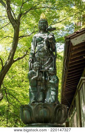 Kanazawa - Japan, June 11, 2017: Hakuju Kanzenon Bodhisattva statue with an old couple at the foot of the Buddhist deity in front of the Hase-san Kannon-in temple in Kanazawa