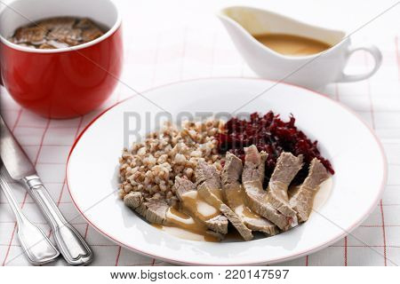 Boiled beef meat with buckwheat porridge, beetroot salad, and beef broth