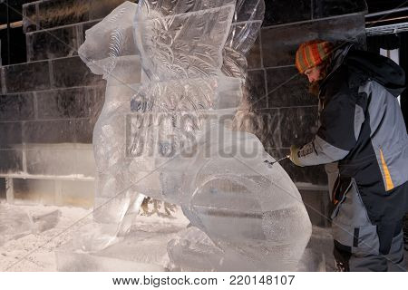 ST. PETERSBURG, RUSSIA - DECEMBER 19, 2017: Sculptor Dmitry Klimenko prepares the statue of griffin for the opening of the festival Ice Fantasy - 2018. 180 tonnes of ice was used for ice compositions