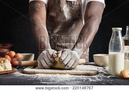 Cropped Shot Of Talented Dark Skinned Male Cook Kneads Studiously Dough, Prepares For Culinary Compe