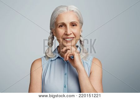 Cheerful Senior Woman With Grey Hair Tied In Pigtails, Has Happy Expression And Broad Shining Smile,